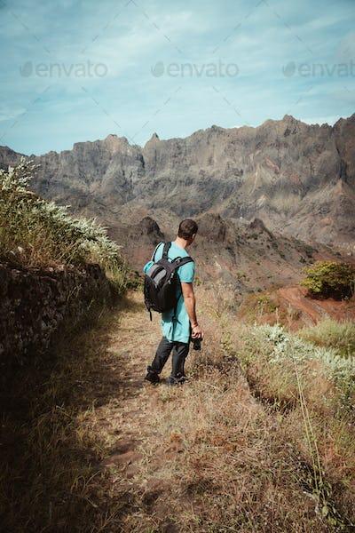 Hiker admiring barren natural landscape in front of rugged mountain range. Trekking trail on one