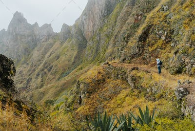 Traveler with camera in front of the monumental mountain ridge and ravine on the cobbled path to Xo