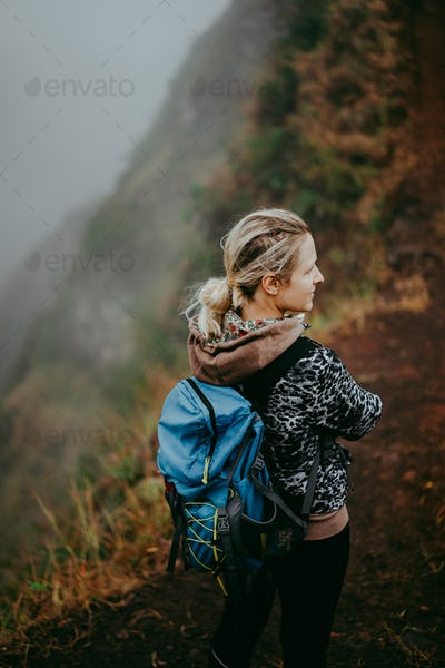 Close up of woman hiker with blue backpack on the narrow misty path of mountain ridge on Santo Antao