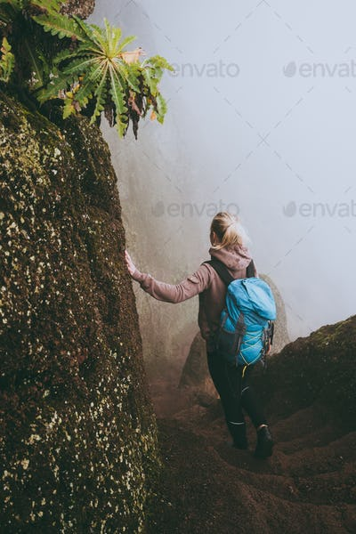Santo Antao. Cape Verde. Girl with blue backpack hike down the steep slope of the rock in the foggy