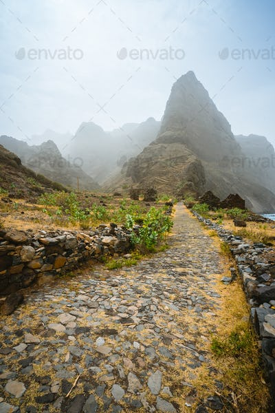 Aranhas mountain peak in the valley with house ruins and stony hiking path going up the mountain