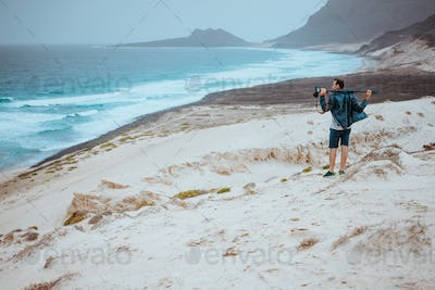 Photographer admitting unique others worldly landscape of sand dunes volcanic cliffs on the Atlantic