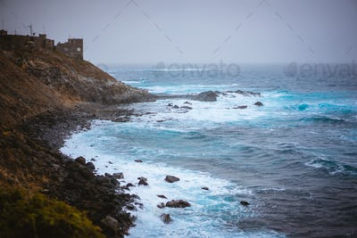 Bluff volcanic coastline in Sinagoga with stormy atlantic ocean. Trekking trail from Ponta do Sol to