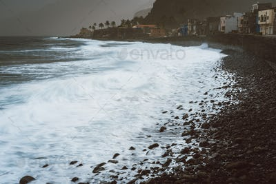 Rough ocean waves with blowing spray rolling onto the rocky volcanic shore. Ribeira Grande Village