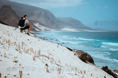 Photographer with camera enjoying quaint moment in scenic coastal landscape of sand dunes and