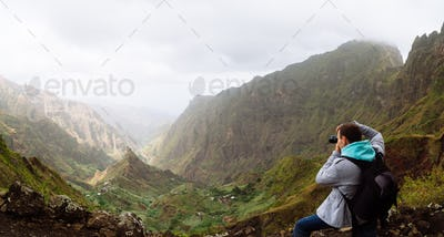 Traveler on the mountain edge making a photo of landscape. Deep clouds above green Xo-Xo Valley