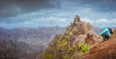 Man hiker with backpack sitting on the mountain top and looking down to the valley. Stunning arid