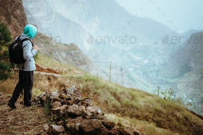Traveler with backpack staying on the edge of path leading through rural landscape with mountains