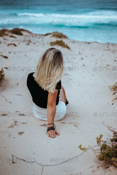 Woman sitting in white sand dune admiring coastline andscape and waves of Atlantic ocean. Sao