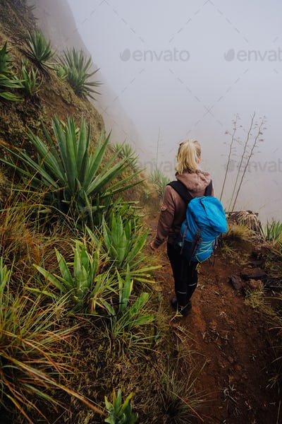 Female traveler staying on the edhe of inactive cove volcano crater above the foggy green valley