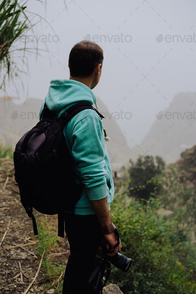 Traveler holding camera stand in front of rural landscape with mountains and the ravine of Paul