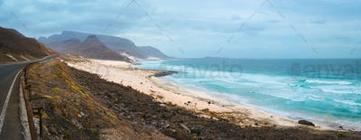 Road along atlantic coastline white sand dunes and ocean waves rolling. Road leads between black