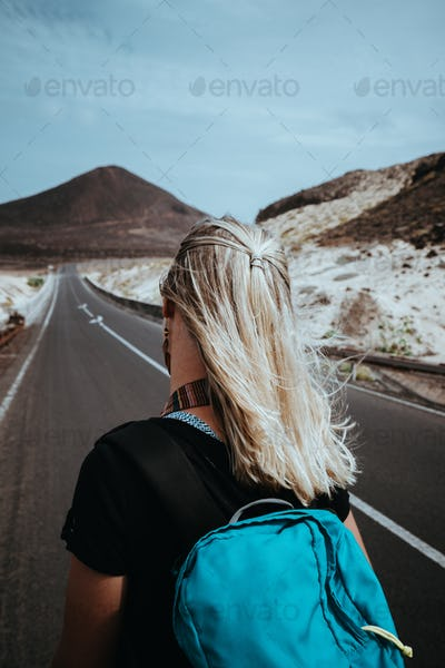 Woman traveler goes on desolate straight road over a surreal landscape with majestic volcano in the