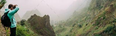 Traveler holding up the camera to take a photo of amazing steep mountainous terrain with lush canyon