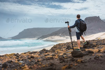 Photographer with camera on tripod in desert admitting unique landscape of sand dunes volcanic