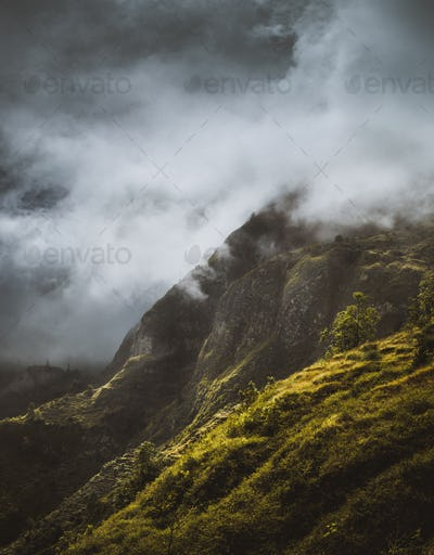 Stunning scenery with mist flowing over huge mountain slope and spilling into the green valley