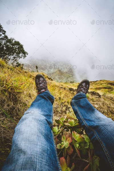 Traveler hiking boots over impressive verdant Xo-Xo valley with mountain peaks, rugged cliffs in fog