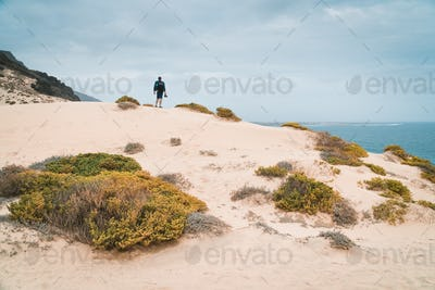 Ttraveler and photographer on the top of snow-white dune landscape on the Atlantic coastline. Sao