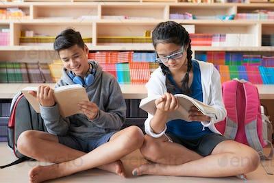 Teenagers sitting on floor reading