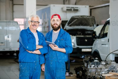 Successful young and mature workers of machine repair service in workshop