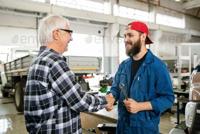 Young cheerful repairman in workswear shaking hand with senior client