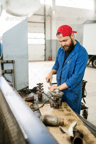 Young professional technician fixing parts of car engine together