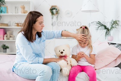Young careful mother touching forehead of her sick little daughter
