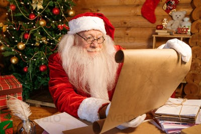 Santa in costume unrolling big paper with Christmas wishes