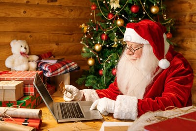 Contemporary Santa in costume sitting by desk in front of laptop at home
