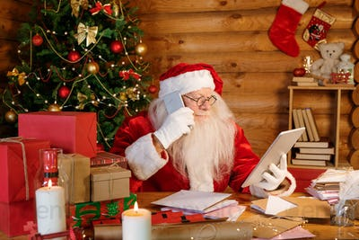 Serious Santa with touchpad and smartphone making online order for Christmas