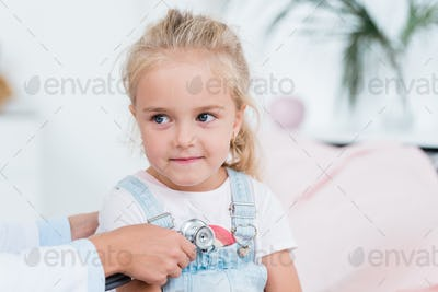 Cute little girl with blond hair looking at doctor using stethoscope