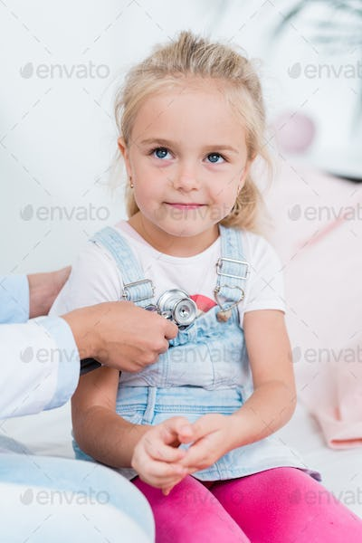 Adorable little girl with blond hair sitting on bed in medical office