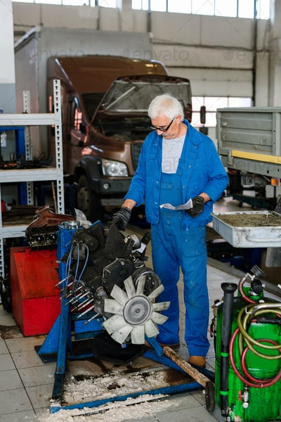 Mature grey-haired master of technical repair service workshop touching engine