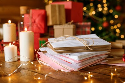 Stack of letters for Santa, three burning candles and group of packed gifts