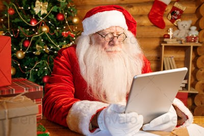 Serious Santa sitting at home by wooden table with tablet in front