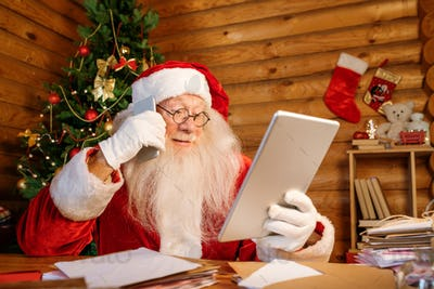 Mobile Santa looking through online xmas presents and making order on smartphone