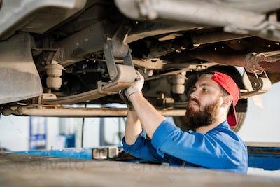 Young bearded technician of machine repair service fixing detail