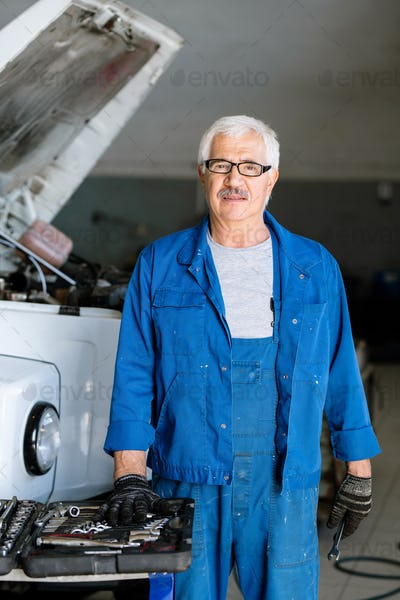 Elderly and experienced master of technical service looking at camera
