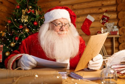 Santa with white beard sitting by table while looking at envelope in his hand