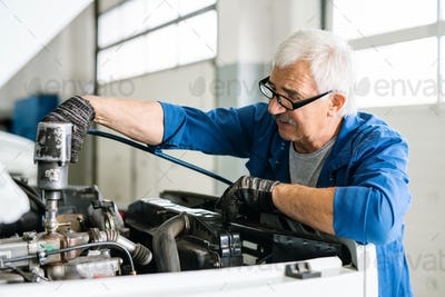 Senior master in workwear and eyeglasses repairing engine of car with drill