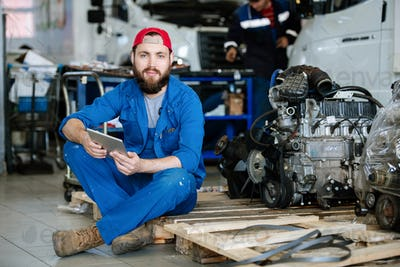 Young bearded worker of machine repair service holding touchpad