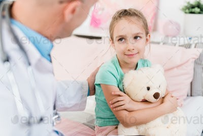 Cute little girl looking at her doctor with smile while listening to him