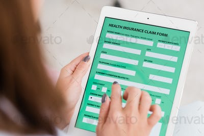 Hands of young woman holding touchpad with health insurance form