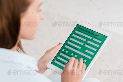 Young woman holding digital tablet with electronic form of health insurance