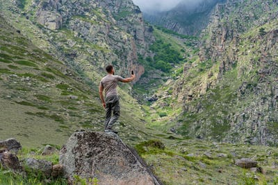 Male hiker takes photo of beautiful mountains while standing on rock
