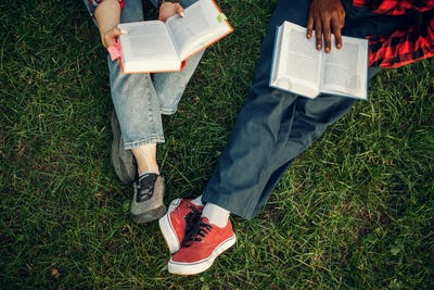 Students with books resting on the grass in park