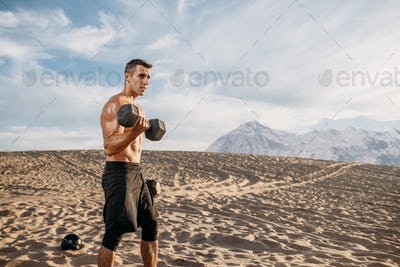 Muscular male athlete with dumbbells in desert
