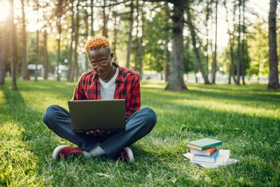 Black student with laptop sitting on the grass
