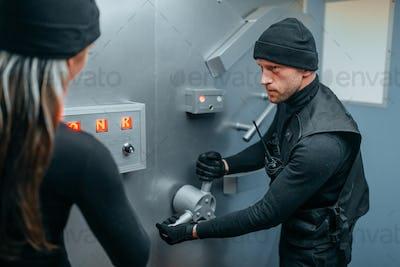 Two robbers in uniform trying to break vault lock