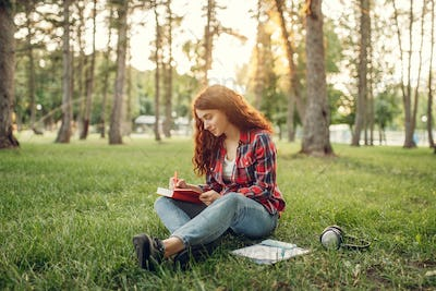 Female student writing in notebook on the grass